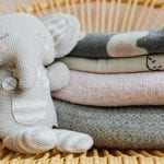 Stack of Baby Receiving Blankets with Baby Toy