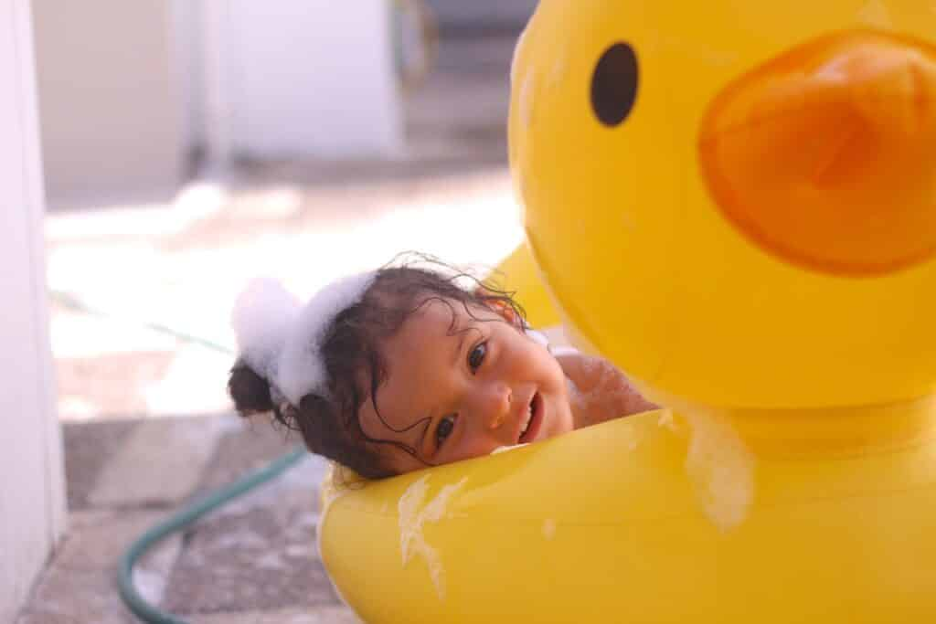 Toddler in duck pool with bubbles in hair for story about Best Toddler Shampoo and Conditioner